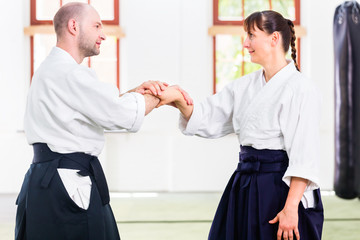 Man and woman fighting at Aikido martial arts school