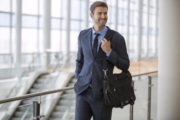 Young businessman walking at the airport with briefcase smiling