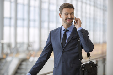 Businessman talking on the phone while standing in the airport