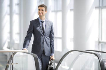 Businessman smiling at the escalator
