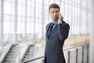 stock-photo-businessman-at-airport-with-mobile-phone