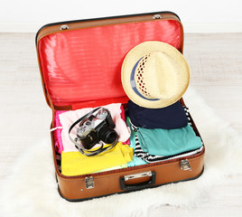Female clothes and photo camera in old suitcase