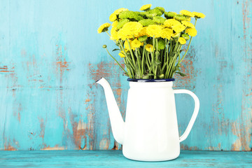 Yellow and green flowers in decorative teapot