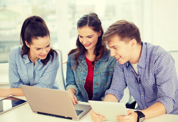 three smiling students with laptop and tablet pc