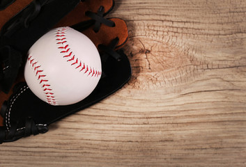 Baseball. Ball in Glove over wood background with copy space.