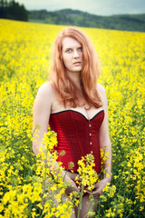 Beautiful redhead in the oilseed Rape