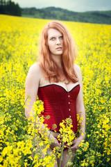Beautiful redhead in the oilseed Rape