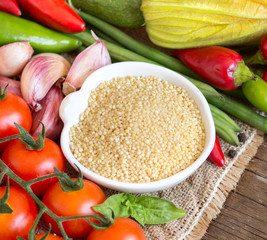 Raw Organic millet in bowl and vegetables