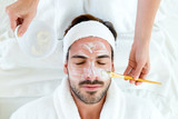 Man with clay facial mask in beauty spa. - 69911281
