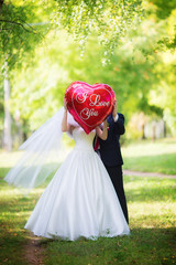 The bride and groom in the Park with the red balloon with the wo