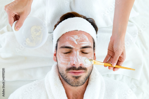 Leinwanddruck Bild Man with clay facial mask in beauty spa.