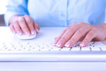 Female hands typing on keyboard, close-up