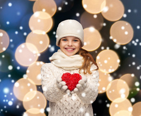 girl in winter clothes with small red heart
