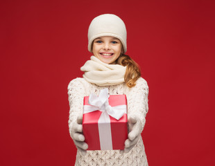 girl in hat, muffler and gloves with gift box