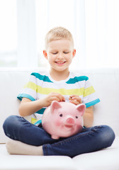 smiling little boy with piggy bank at home