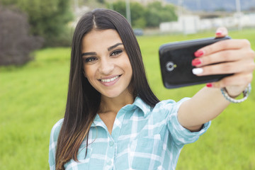 Cute girl taking selfie in park