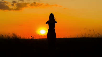 Silhouette of a Girl Practicing Yoga  At Sunset