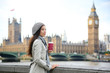 London woman drinking coffee by Westminster Bridge - 69914430