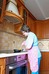 Woman housewife fry food in a pan