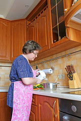 Woman housewife prepares food using a mixer
