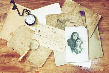 top view of  antique photographs and old pocket clock