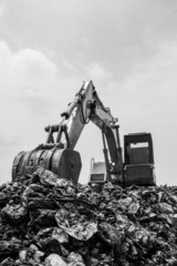 mountain of garbage with working backhoe , monochromatic
