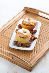 baked stuffed apples on a white plate on wooden tray