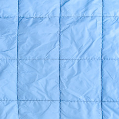 blue silk quilted fabric as a background, closeup