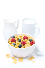 cornflakes with fresh berries in a bowl, milk, isolated