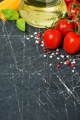dark background with fresh cherry tomatoes, pasta and olive oil