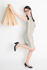 Asian Chinese girl hands holding paper shopping bags