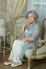 Mature woman sitting in vintage sofa
