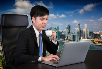 Portrait of goodlooking Asian man sitting at table at working of