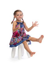 Little girl in a colored dress on a chair