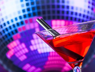 red cocktail and straw with sparkling disco ball background