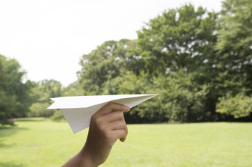 Boy flying a paper airplane in the park