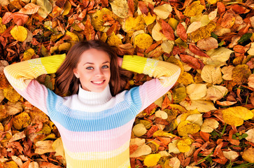 Girl Laying On A Heap Of Yellow Leaves