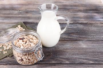 Homemade granola in glass jar and fresh milk in jug,