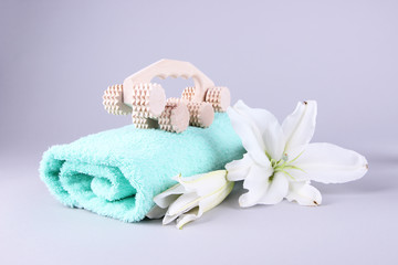 Wooden roller brush, towels and lily on grey background