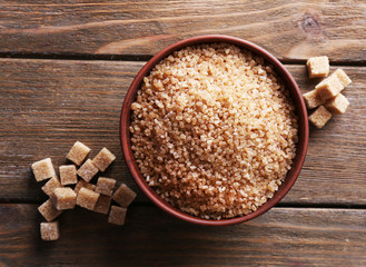 Brown sugar cubes and crystal sugar in bowl on wooden