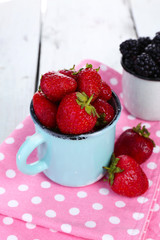 Sweet berries in cup on table close-up