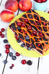 Sweet berries and berry tart on table close-up