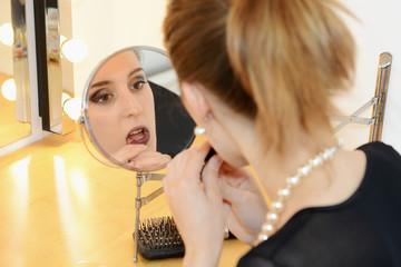 Teenager mit Lippenstift vor Schmink-Spiegel