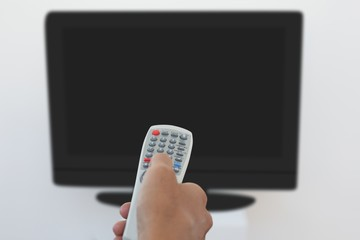 Hand holding remote and changing channel