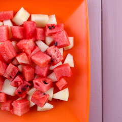 Slices of watermelon in orange plate on wooden background