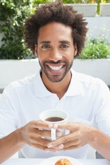 Smiling man having a coffee