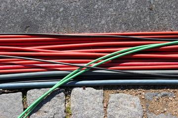 Stromkabel in den Farben Rot, Schwarz und Grün liegen am Boden