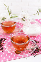 Cups of tea on table on brick wall background