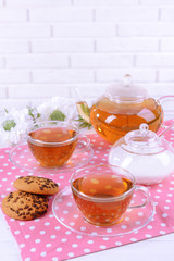 Teapot and cups of tea on table on brick wall background