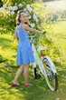 Girl with bicycle in the garden